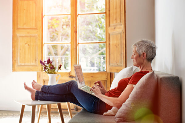 Shot of a mature woman relaxing on her sofa at home using a laptop