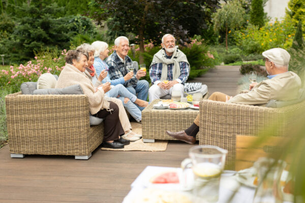 Group of older people sitting on a terrace at friends' house